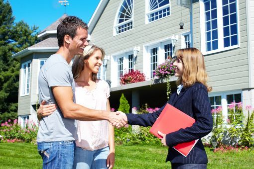 Realtor shaking hands with couple at house